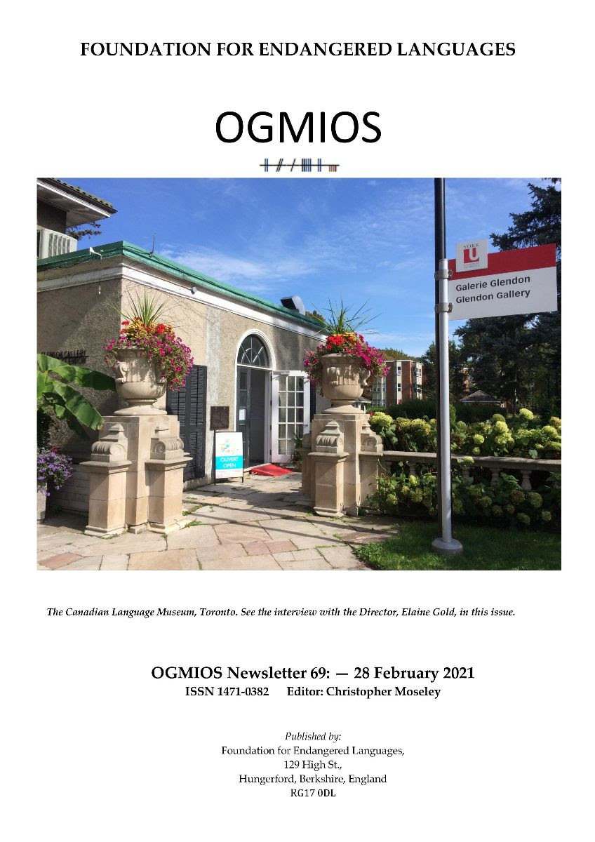 Ogmios cover with the outside of the Museum in the sunshine, door open and flowers blooming
